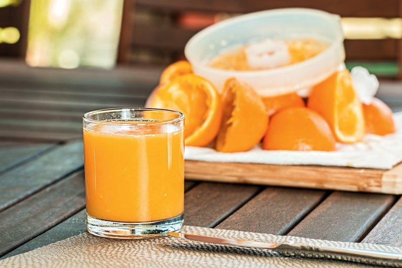 Orangensaft mit Orangen im Hintergrund
