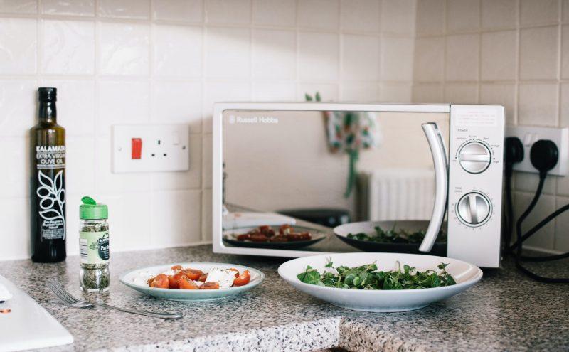 Mikrowelle steht auf einer Küchentheke mit Essen im Vortdergrund