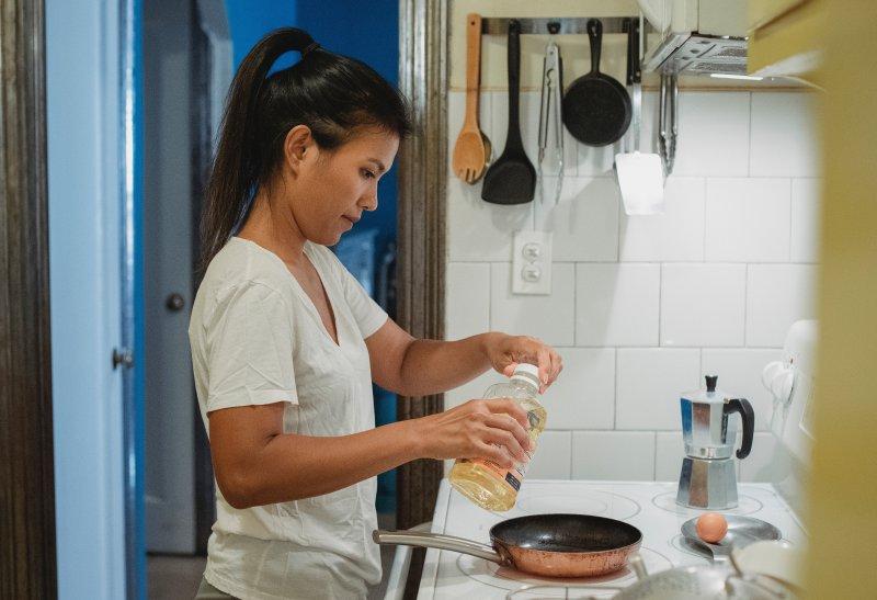 Frau kocht am Herd, im Hintergrund eine Möglichkeit Kartoffelstampfer aufzuhängen