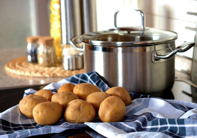 Kartoffeln auf Handtuch neben Kochtopf