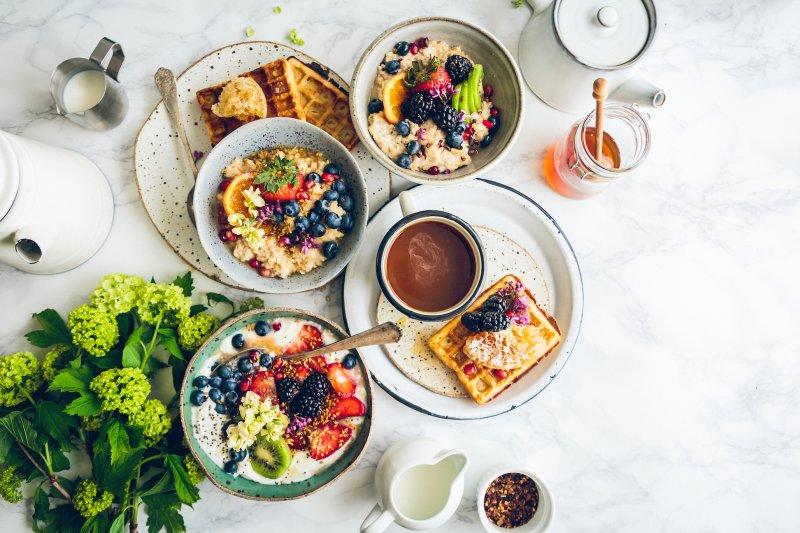 Belgische Waffeln zum Frühstück neben Haferflocken, Obst und Kaffee