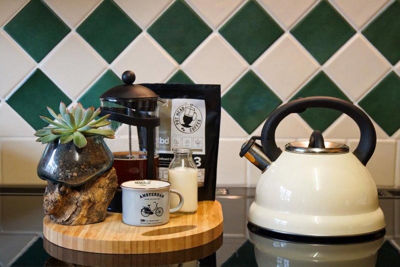 Wasserkessel neben Tablett mit Kaffee auf Herd