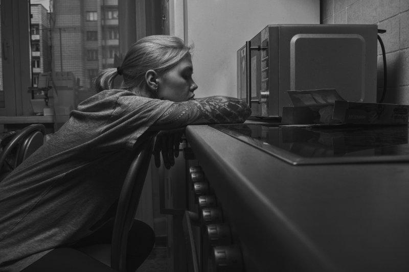 Frau sitzt vor einer Mini Mikrowelle