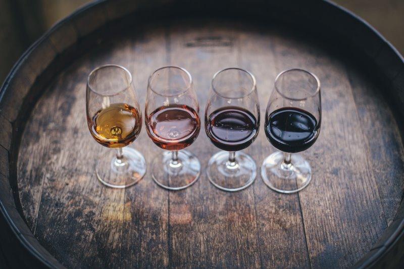 Vier Weingläser mit unterschiedlichen Weinen stehen in einer Reihe auf einem Weinfass
