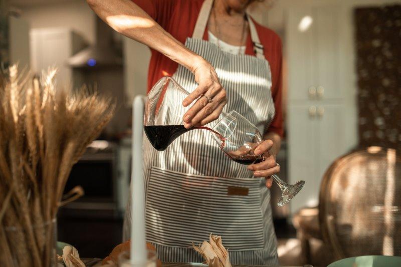 Eine ältere Dame mit Schürze schenkt Rotwein aus einem Weindekanter in ein Weinglas