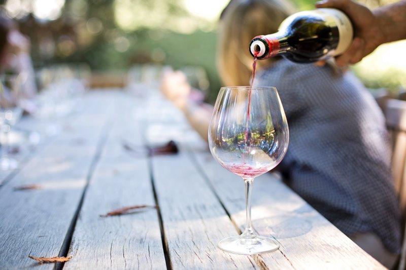 Rotwein wird aus einer Flasche in ein Glas geschenkt