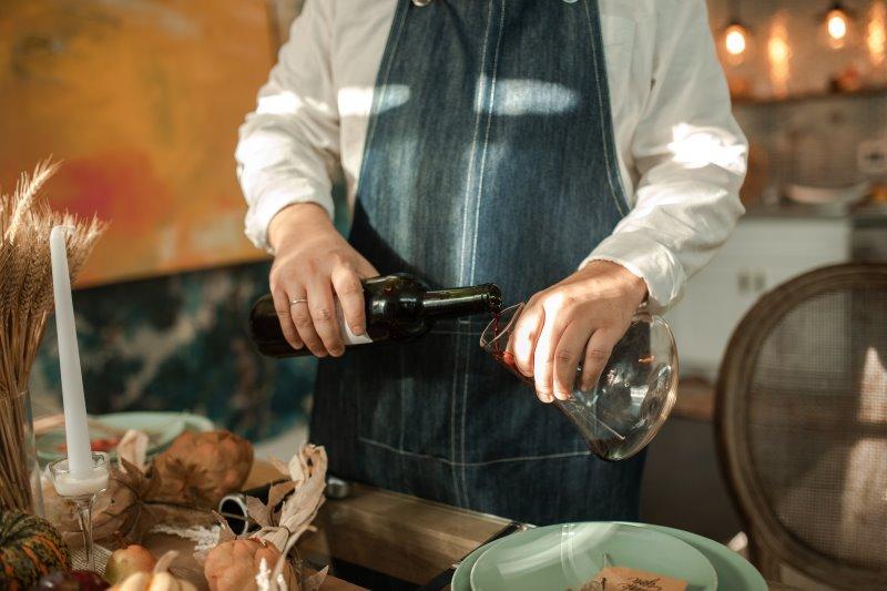 Ein Herr mit Schürze füllt Rotwein von der Flasche in einen Weindekanter