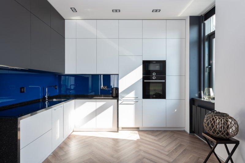Bild auf dem ein autarker Backofen in einer weißen Küche mit blauen Elementen zu sehen ist.