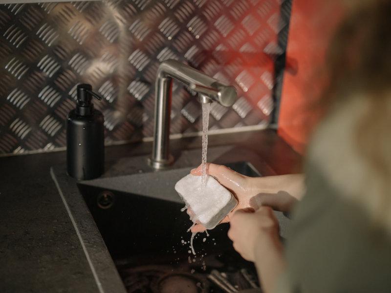 Wasser und Spülschwamm mit dem die Partypfanne gereinigt werden kann