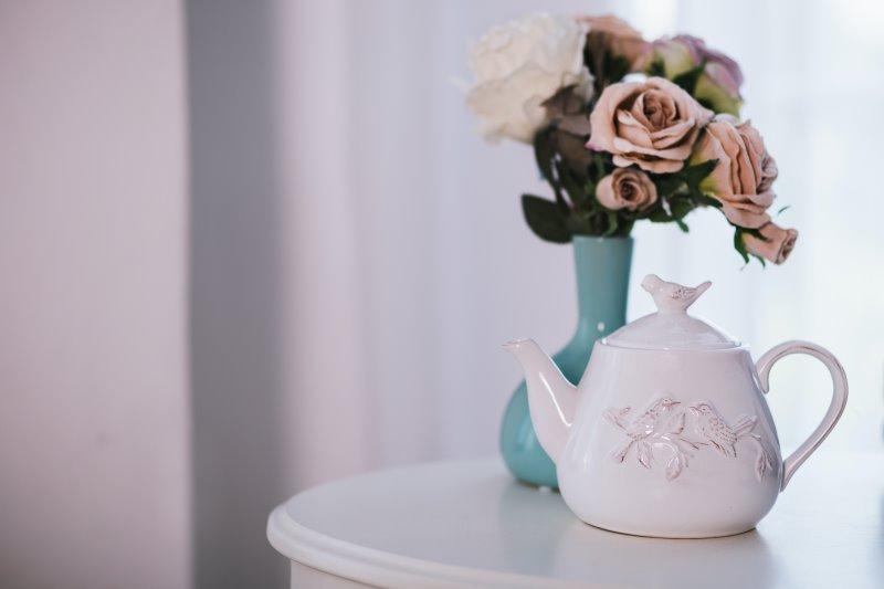Eine weiße Keramik-Teekanne mit Blumen auf einem Tisch